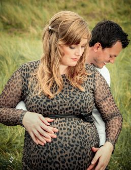 Zwangerschap fotoshoot vrouw en man in duinen met handen op buik