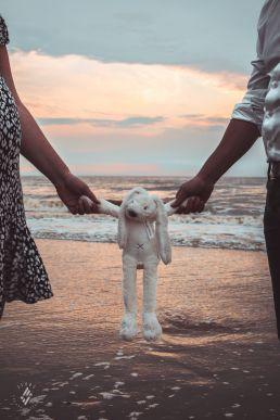Zwangerschap fotoshoot handen houden knuffelkonijn vast voor ondergaande zon in de zee